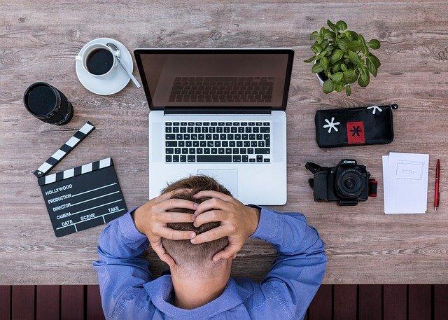 Muž s hlavou v dlaních u notebooku